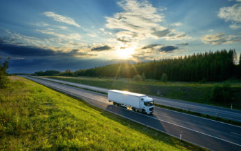 White truck driving on the highway in the countryside in the rays of the sunset with dramatic clouds